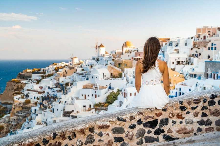 Girl in a white dress sitting in the Oia Castle, Santorini