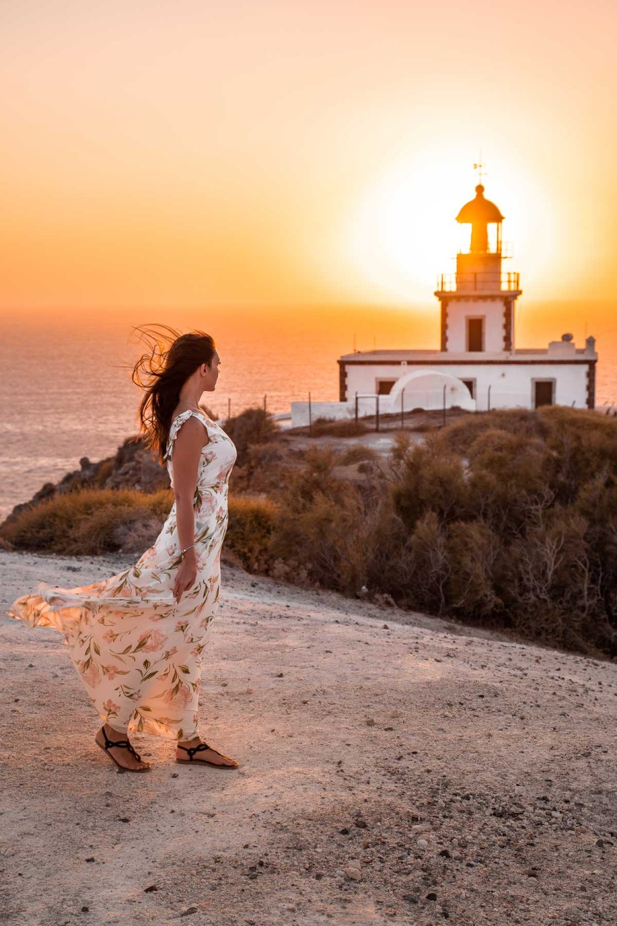Girl in a floral dress watching the sunset at the Akrotiri Lighthouse in Santorini