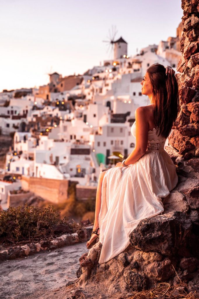 Girl in a white dress sitting in a cave, watching the sunset in Oia, Santorini