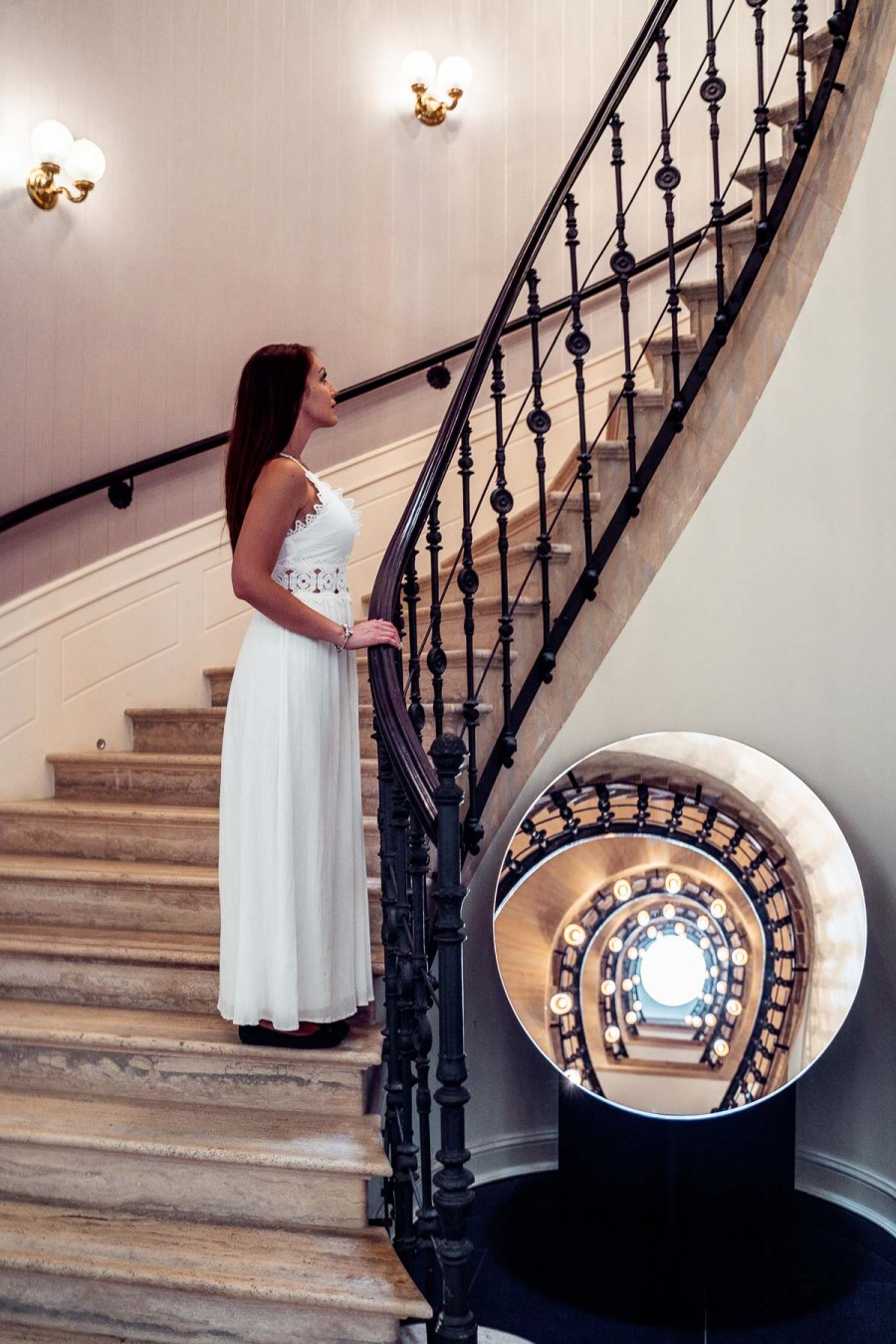 Girl in a white dress standing on a stairway at the Aria Hotel in Budapest