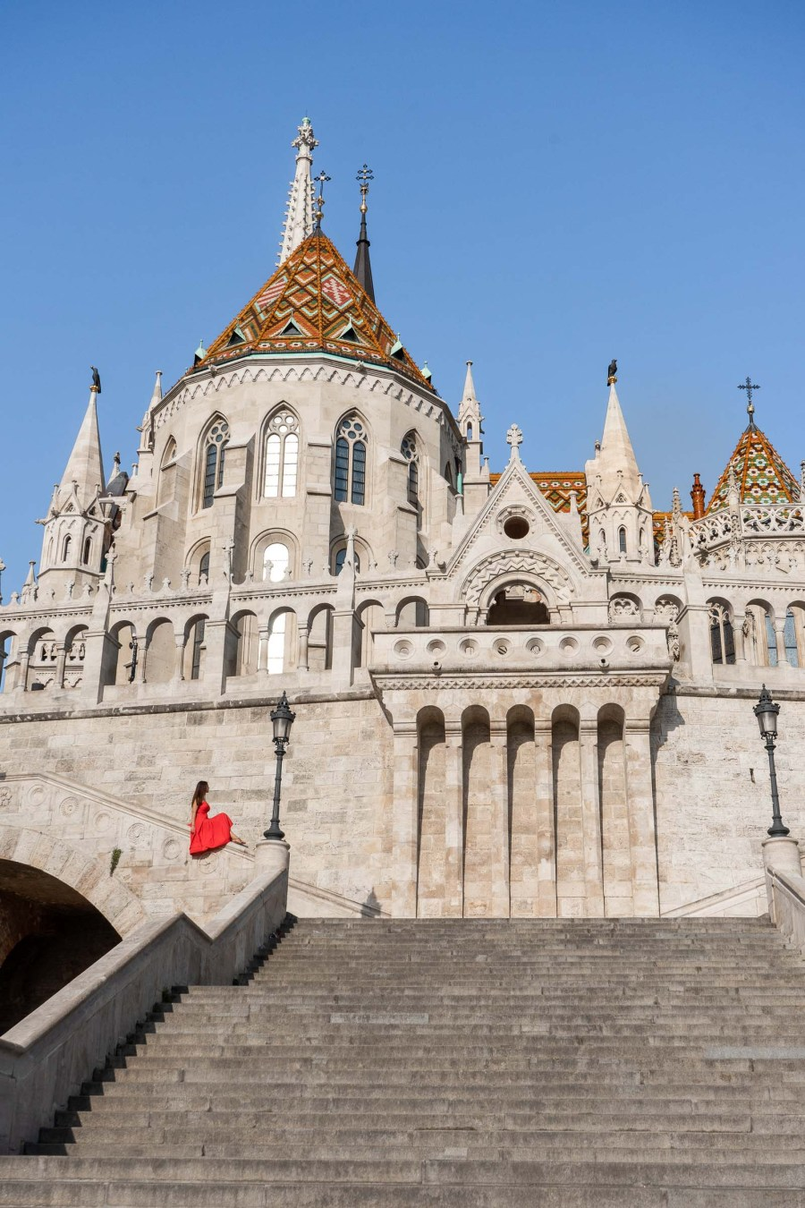 Girl in a red dress sitting at the Fisherman's Bastion in Budapest