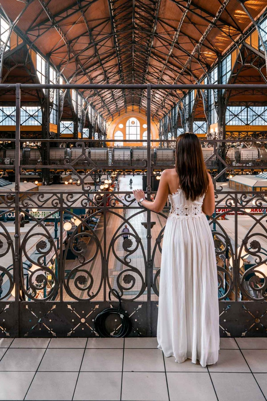 Girl in a white dress standing in the Great Market Hall in Budapest