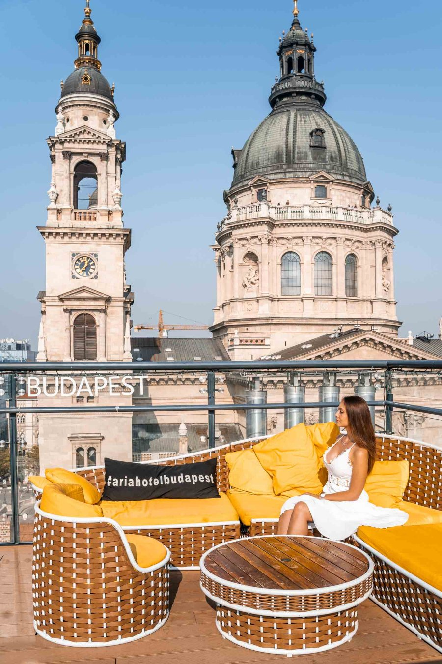 Girl in a white dress sitting in a yellow sofa at the High Note Skybar with the St. Stephen Basilica in the background