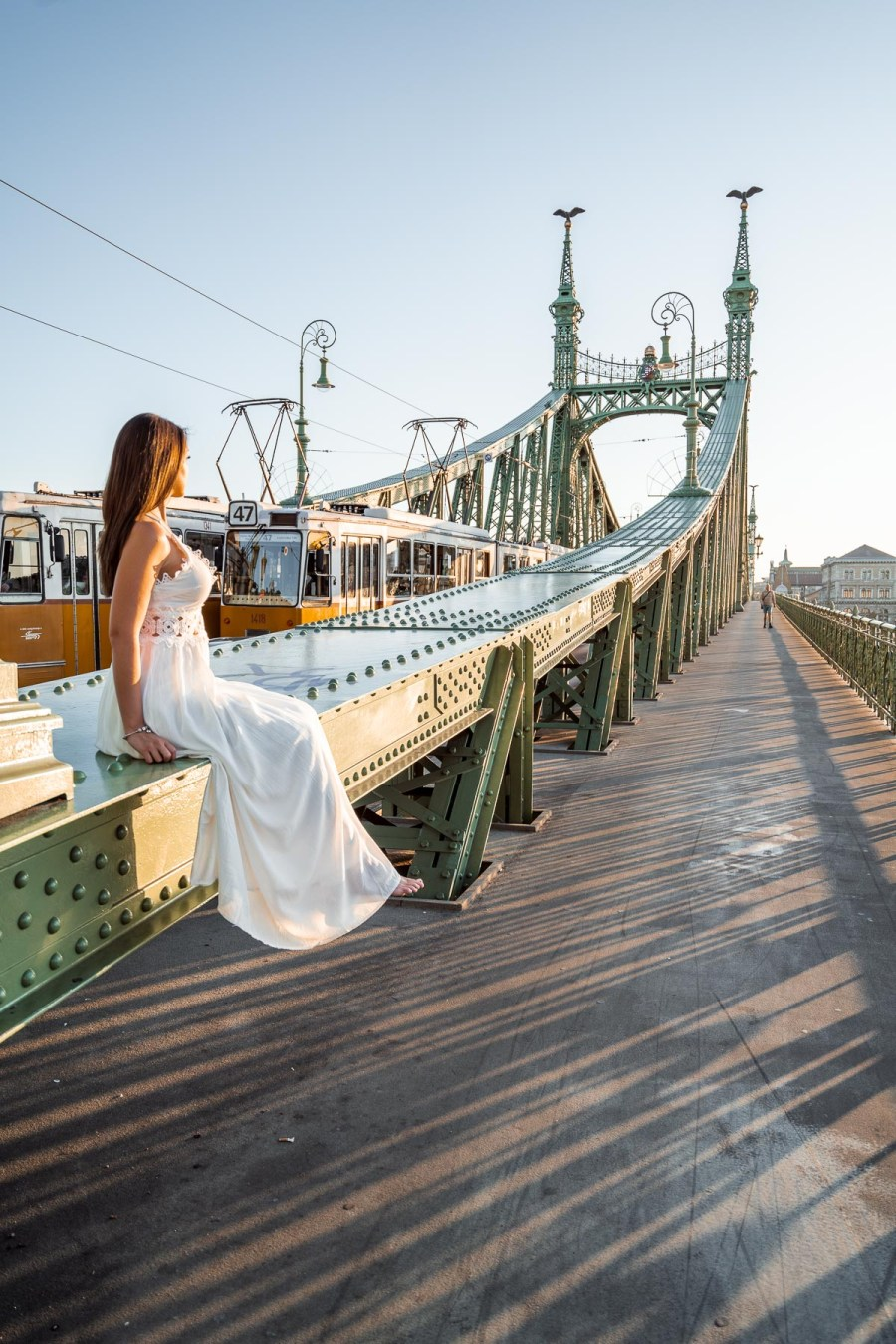 Girl in a white dress sitting on the Liberty Bridge in Budapest