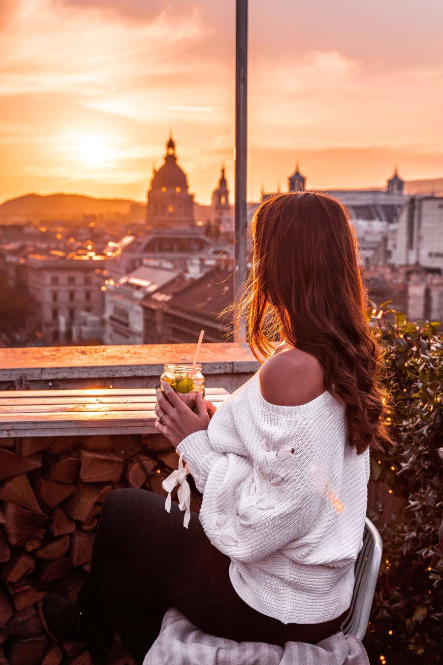 Girl in a white sweater looking at the sunset from the 360 Bar in Budapest