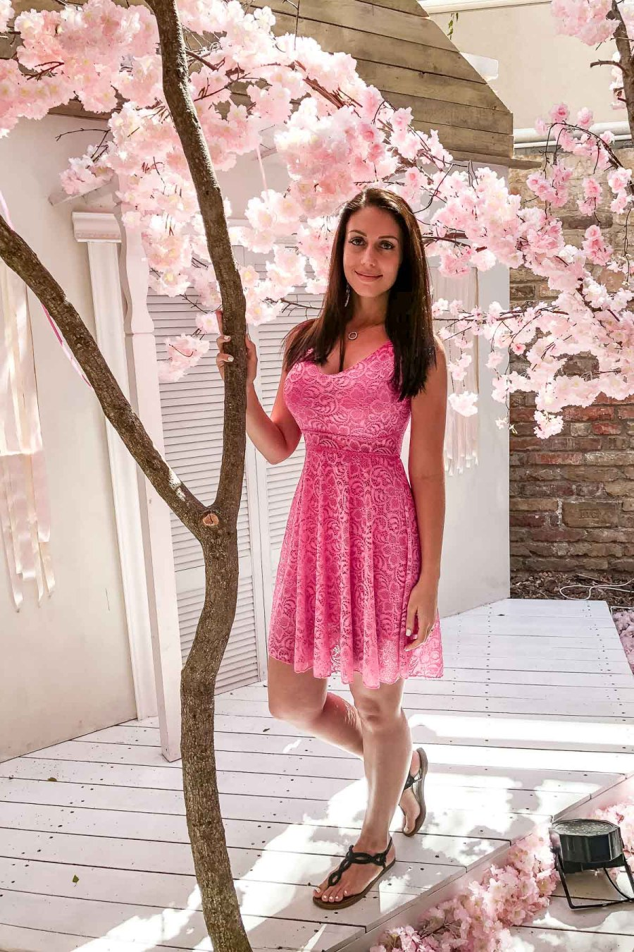 Girl in a pink dress standing under the cherry blossom trees at the Vintage Garden in Budapest