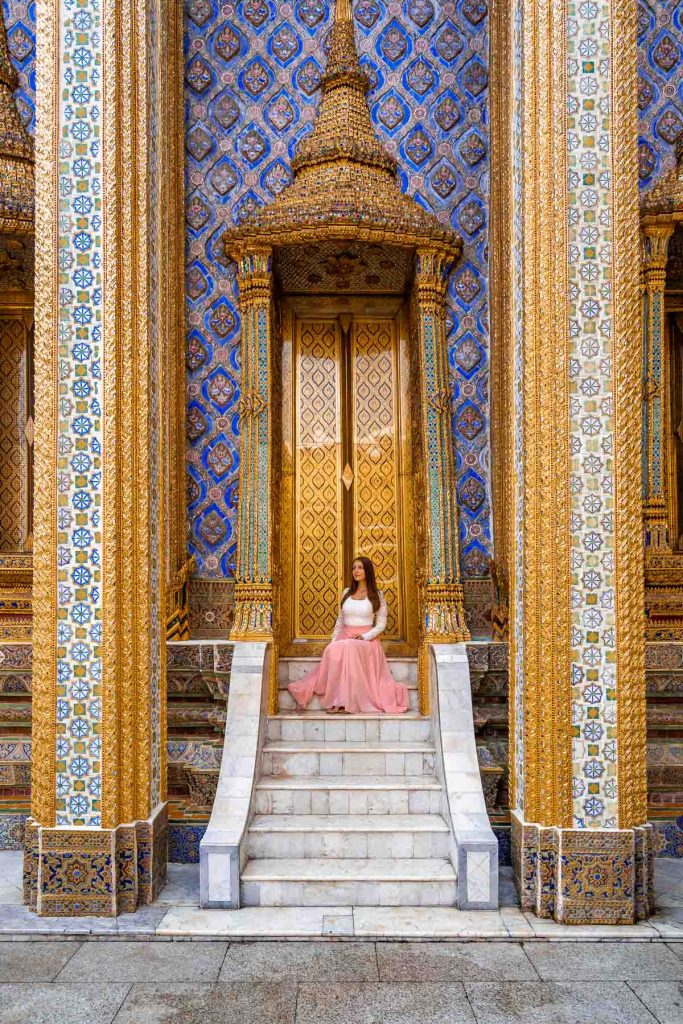Girl in a pink skirt sitting on the stairs at the Grand Palace in Bangkok, Thailand