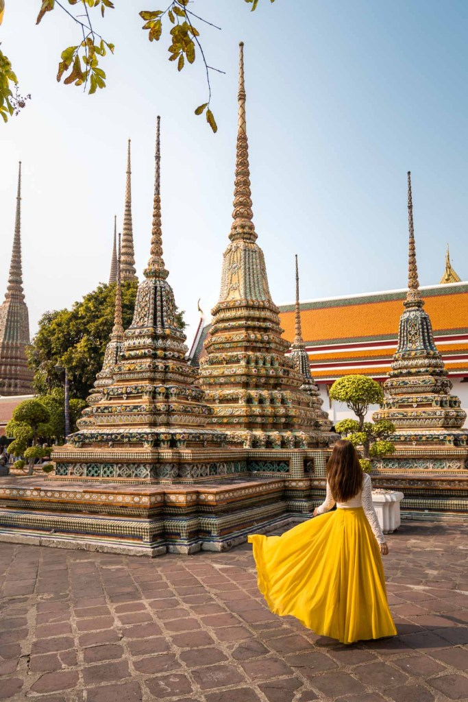Girl in a yellow dress standing in front of the beautifully decorated stupas at the Wat Pho in Bangkok