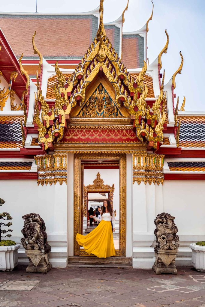 Girl in a yellow dress standing inside the Wat Pho in Bangkok