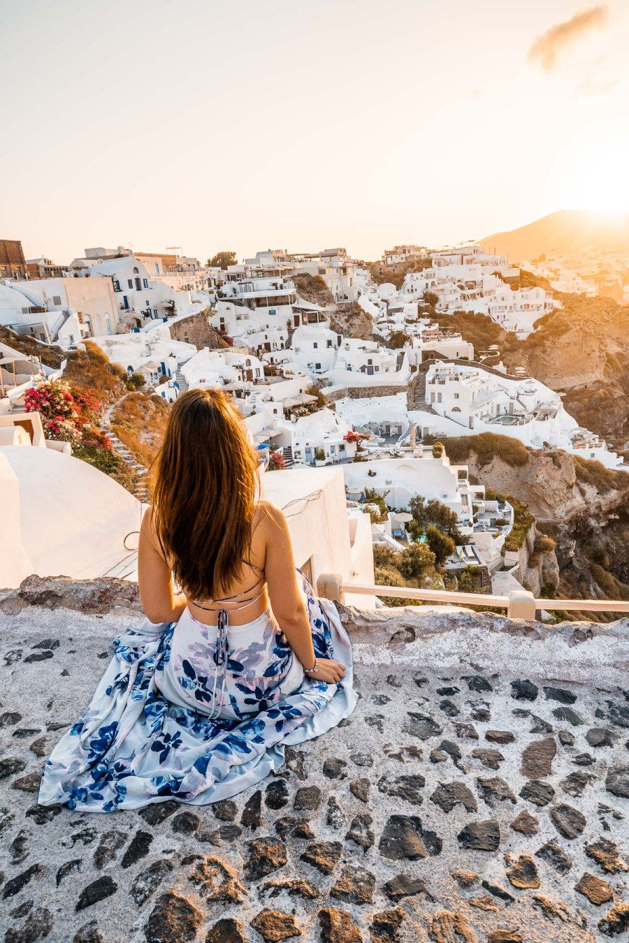 Girl in a blue floral dress sitting on a stone pathway, watching the sunrise in Oia, Santorini