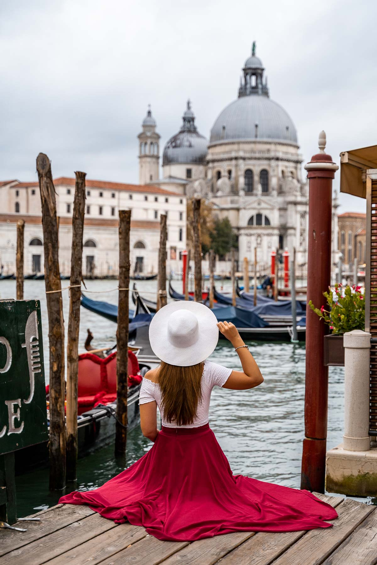 Girl in a red skirt sitting on a pier looking at Santa Maria della Salute in Venice, Italy