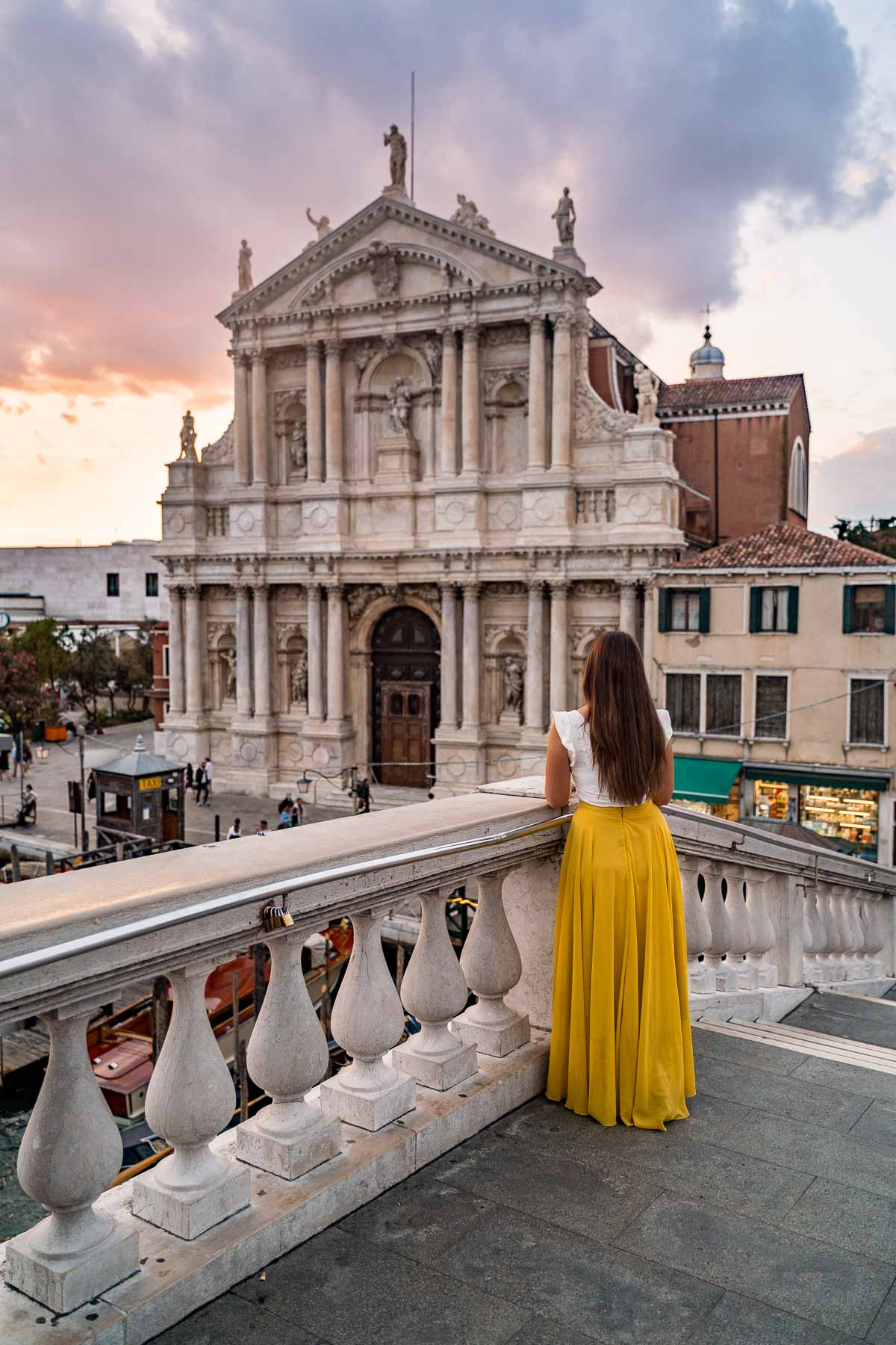 Girl in a yellow skirt watching the sunset at Ponte degli Scalzi in Venice