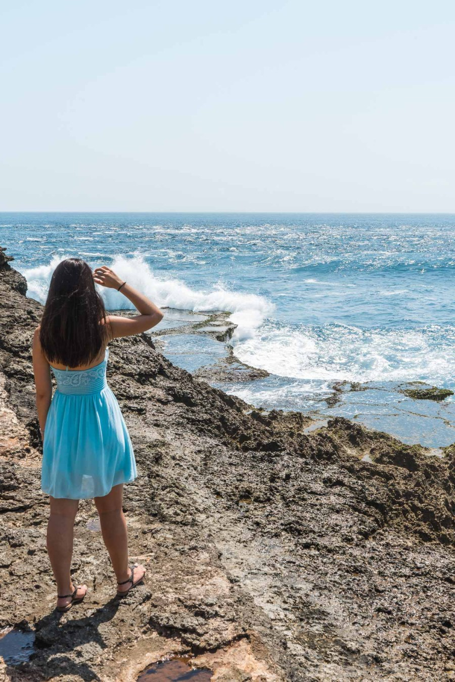 Girl in a blue dress standing at Devils Tear on Nusa Lembongan