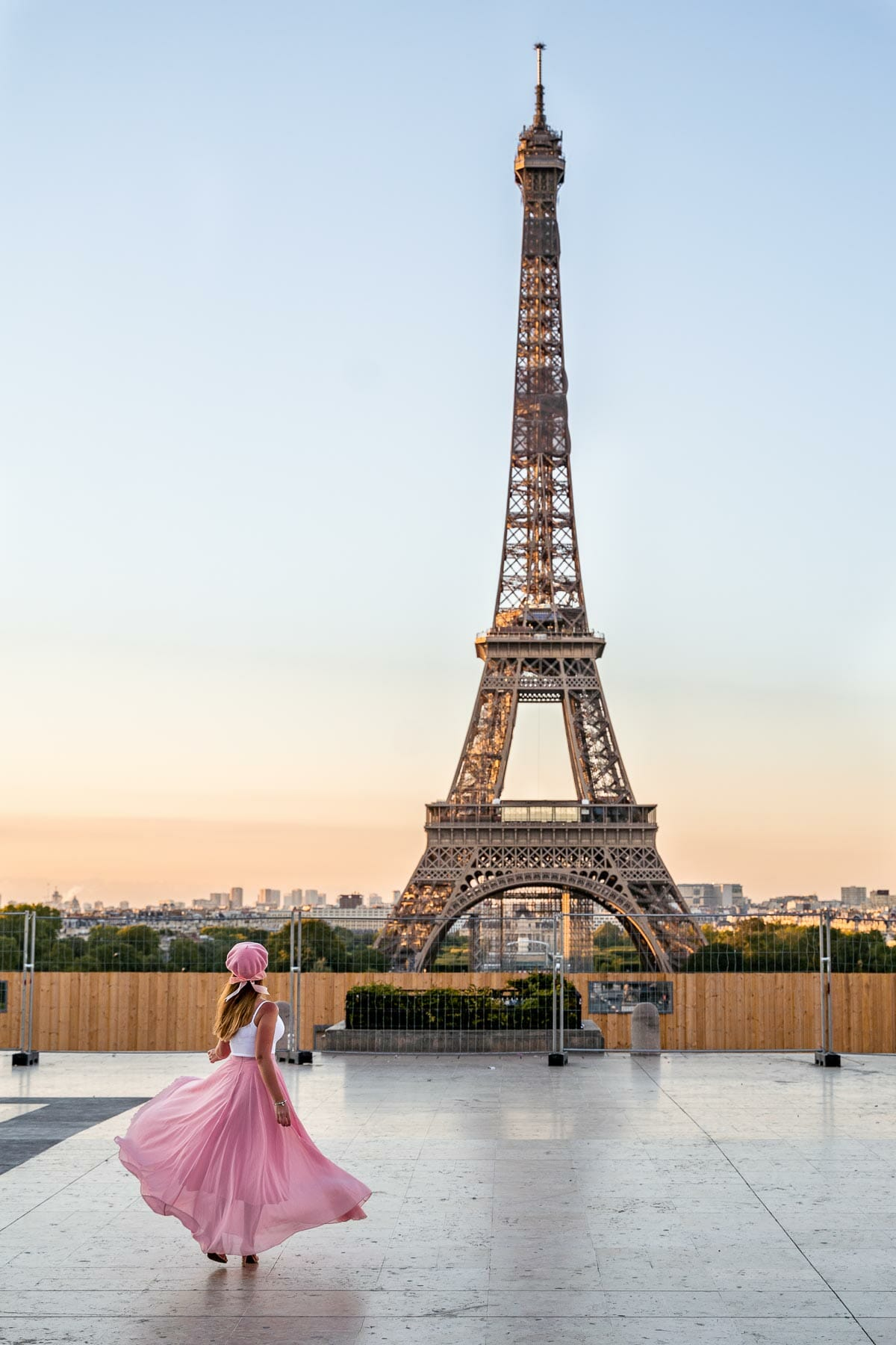 Girl in a pink skirt twirling in front of the Eiffel Tower at Trocadero, one of the most instagrammable places in Paris