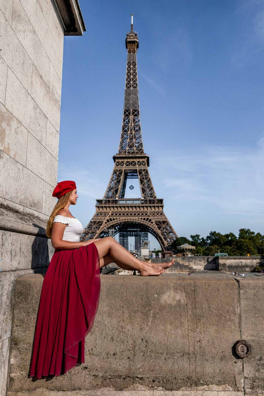 Girl in a red skirt and beret sitting on Pont d'Léna, looking at the Eiffel Tower