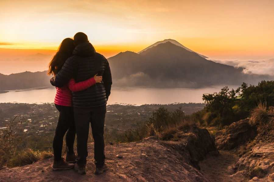 Girl and a boy watching the sunrise from Mount Batur in Bali