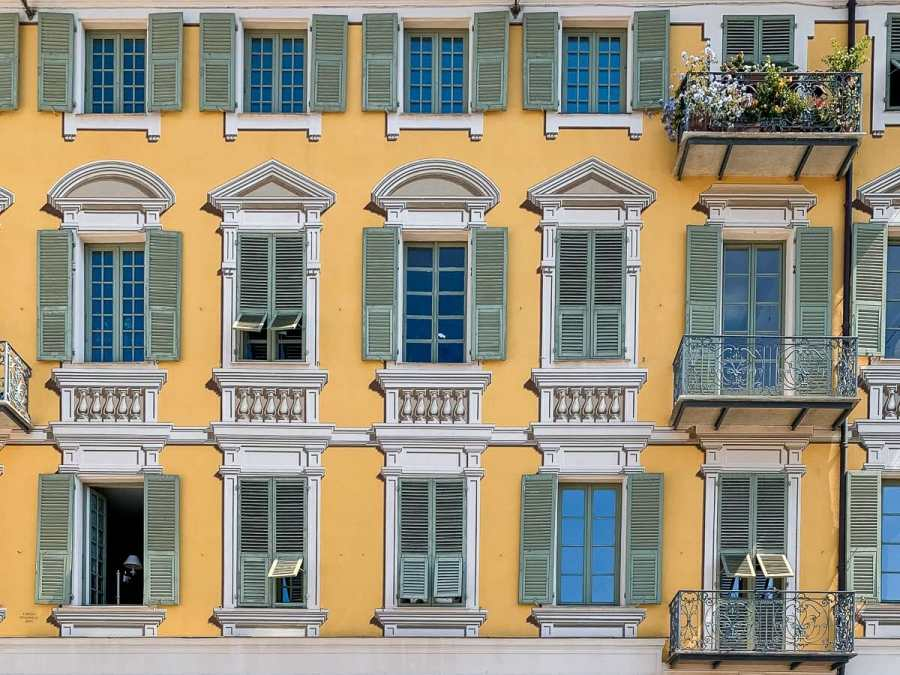 Close-up photo of a yellow building with green shutters at Place Garibaldi in Nice, France