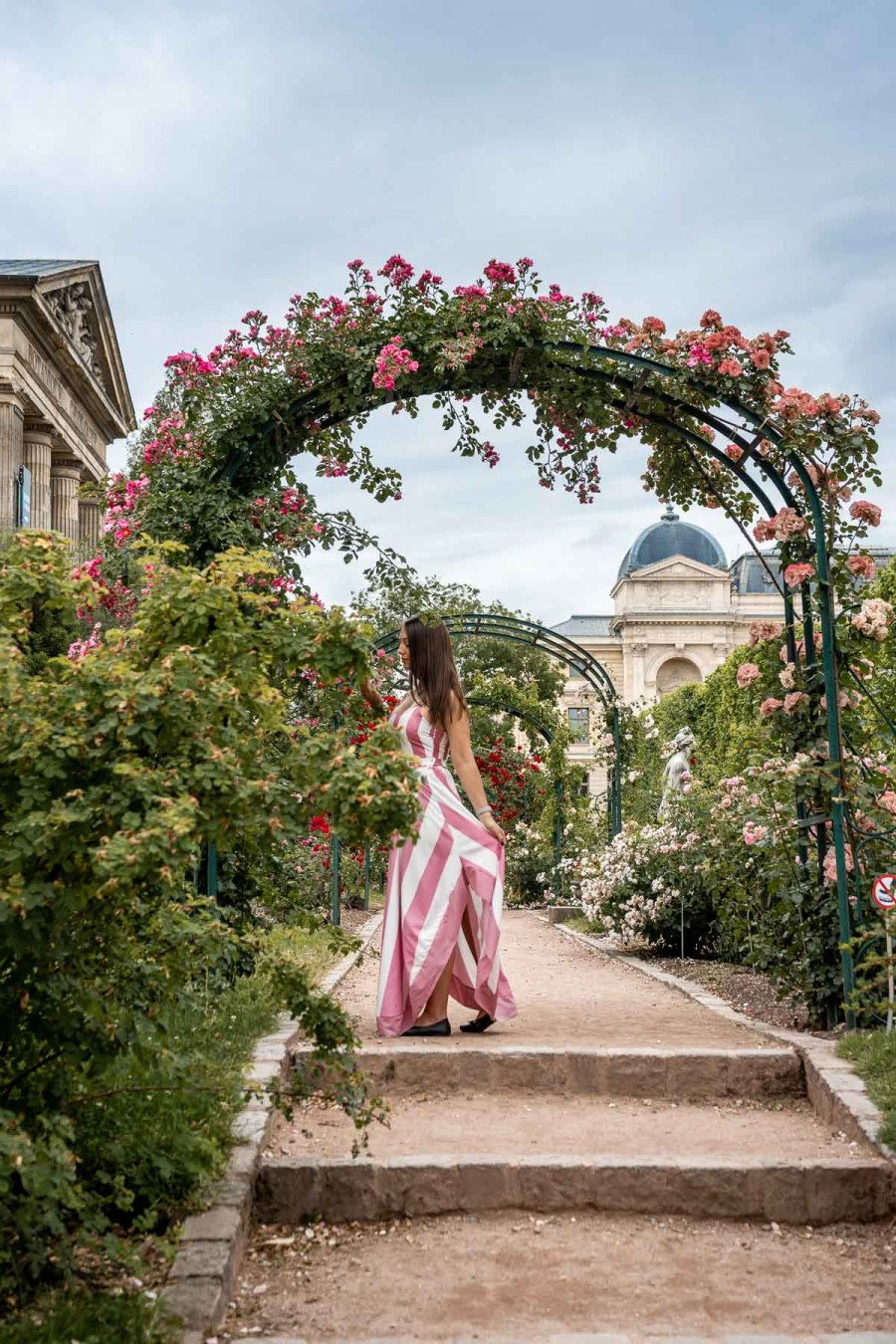 Girl in a pink-white striped dress standing under an archway of roses at Jardin des Plantes in Paris, France