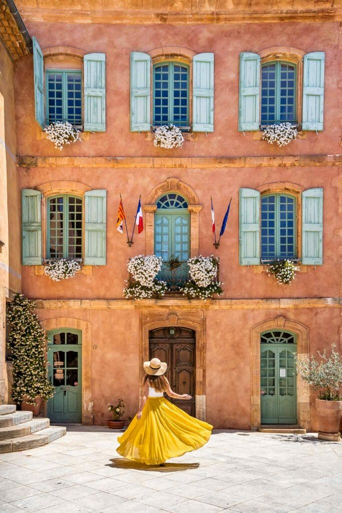Girl in a yellow skirt twirling in front of the cute looking courthouse in Roussillon, Provence