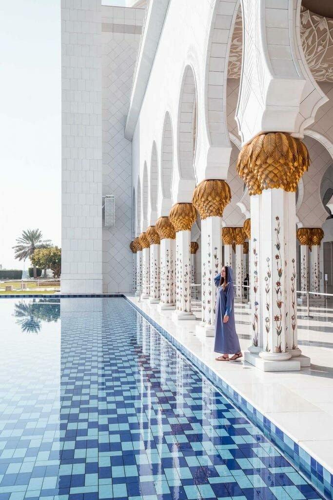 Girl in a blue abaya standing by the pool in Sheikh Zayed Grand Mosque, Abu Dhabi