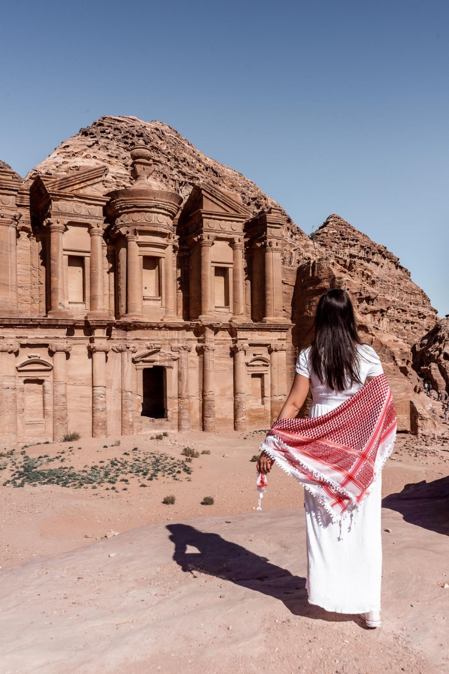 Girl in a white dress standing in front of the Ad Deir Monastery in Petra, Jordan