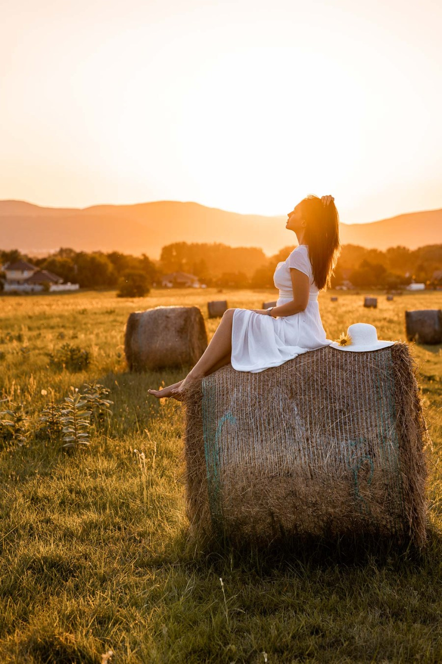 Girl in a white dress sitting on a haystack at sunset