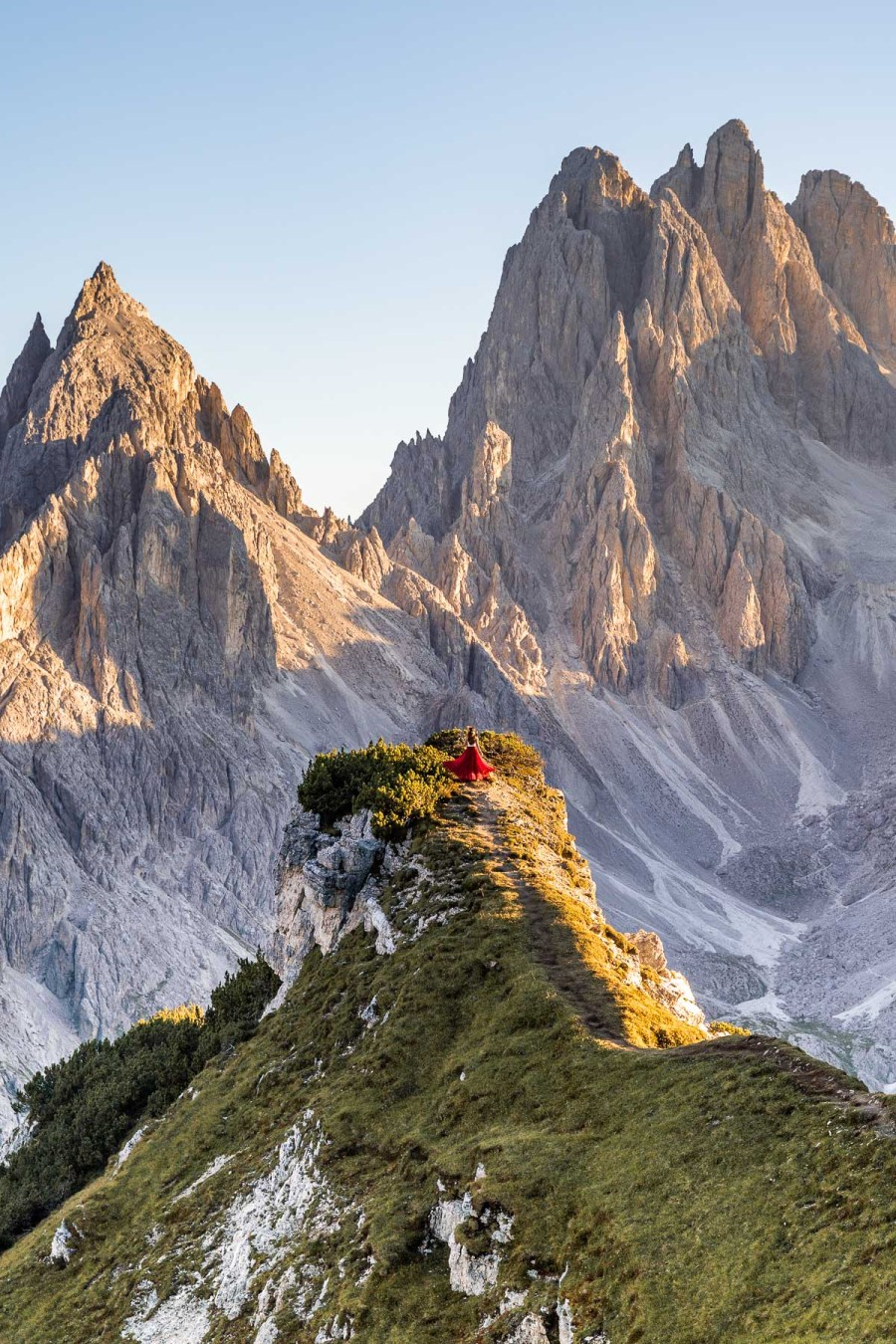 Girl in a red dress standing on top of an epic viewpoint at Cadini di Misurina in the Italian Dolomites