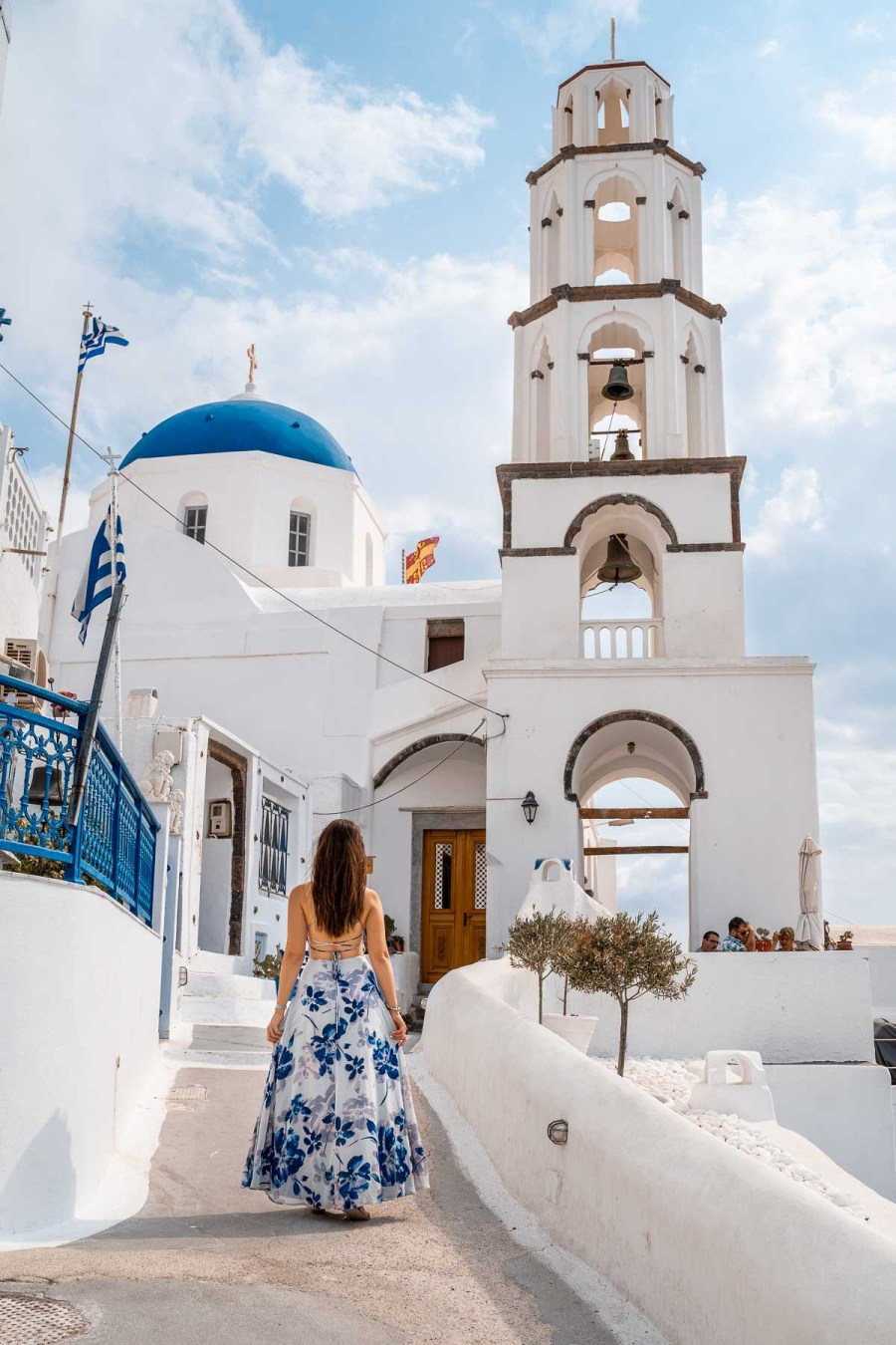 Girl in a blue floral dress standing in front of a church in Pyrgos, Santorini