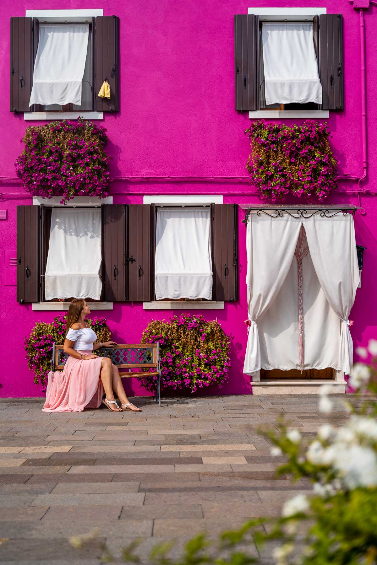 Girl in a pink skirt sitting in front of a pink house in Burano