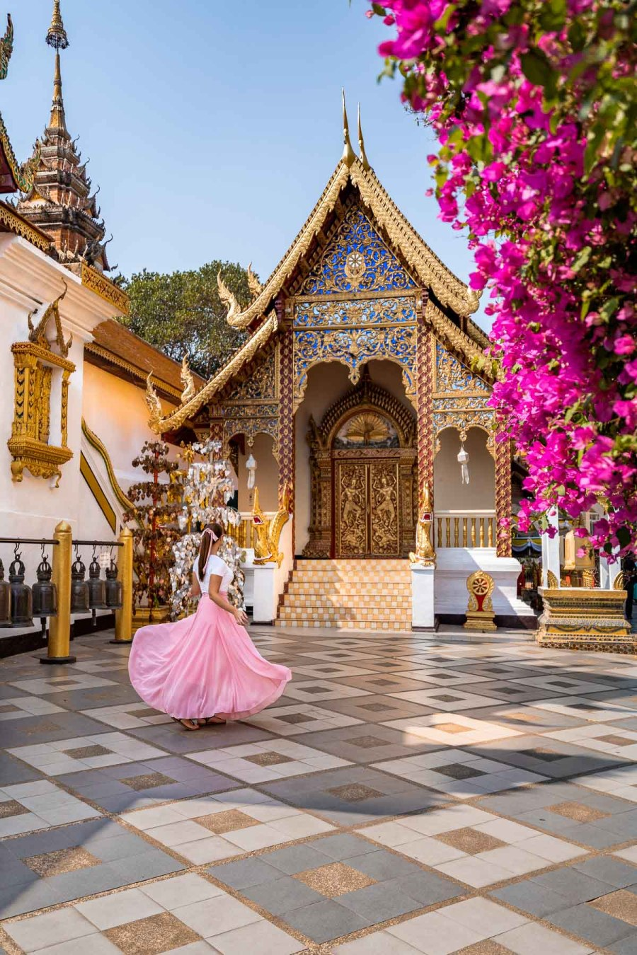 Girl in a pink skirt twirling in front of a beautiful temple in Doi Suthep, Chiang Mai