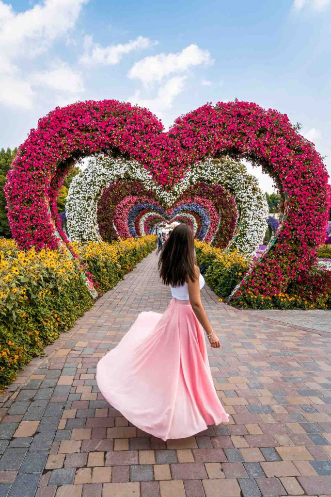 Girl in a pink skirt twirling in front of a pink heart shaped tunnel in the Dubai Miracle Garden