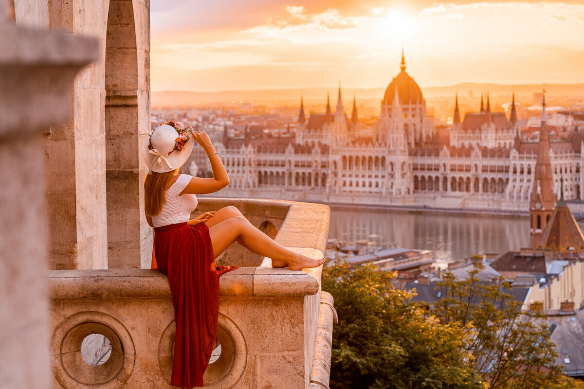 Girl in a red skirt sitting on the balcony at Fisherman's Bastion, watching the sunrise in Budapest