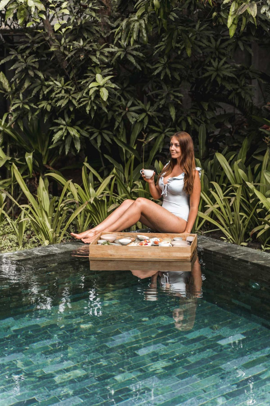 Girl in a blue swimsuit having a floating breakfast at Templation Siem Reap