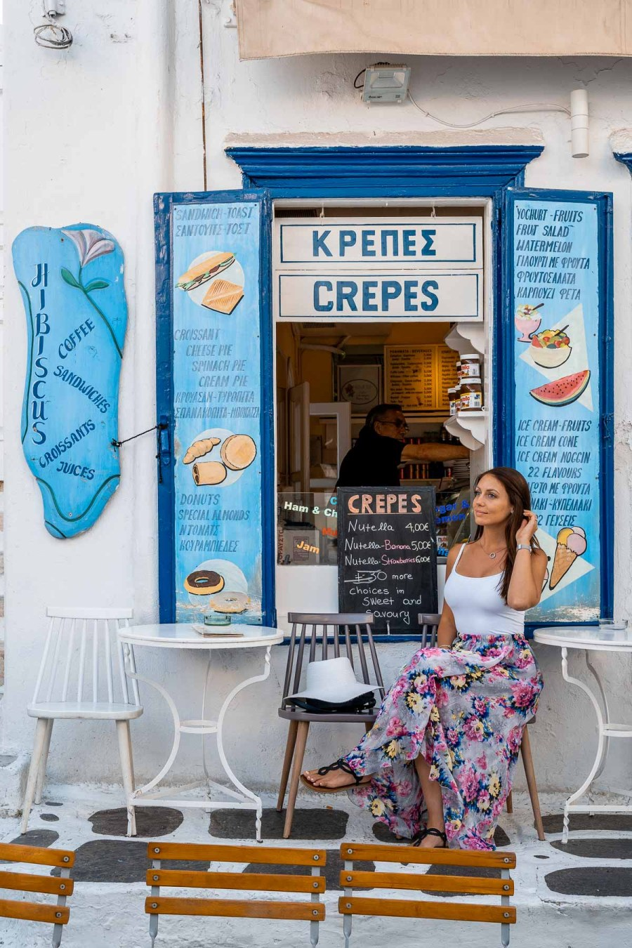 Girl in a purple floral dress sitting in front of the Hibiscus Fruit Parlor in Mykonos