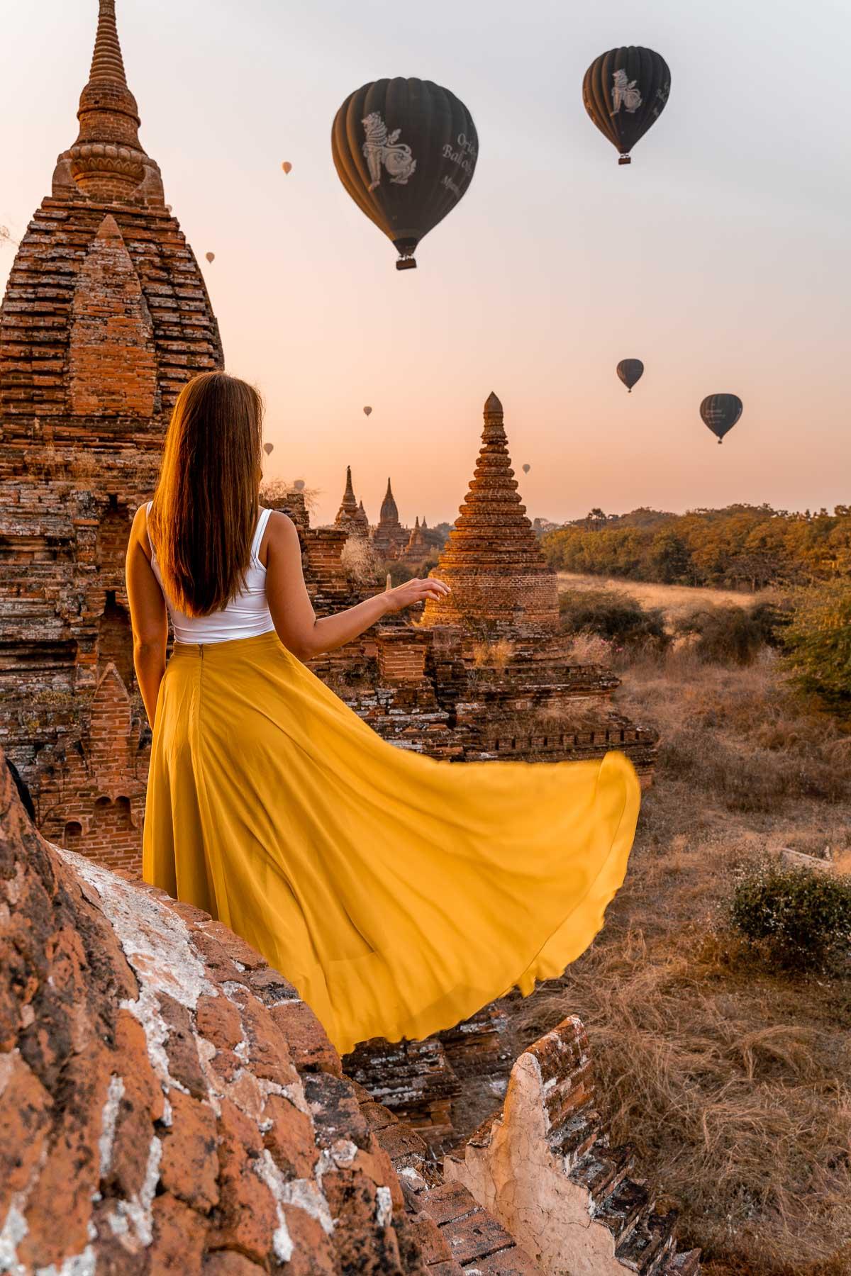 Girl in a yellow dress watching the hot air balloons at sunrise in Bagan, Myanmar