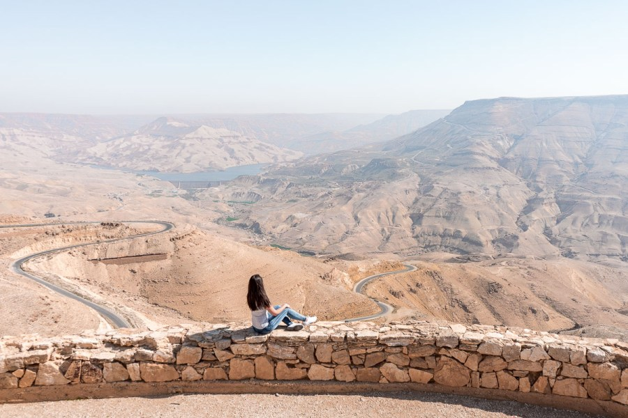 Girl in a white T-shirt and jeans looking at the winding roads of the King's Highway in Jordan