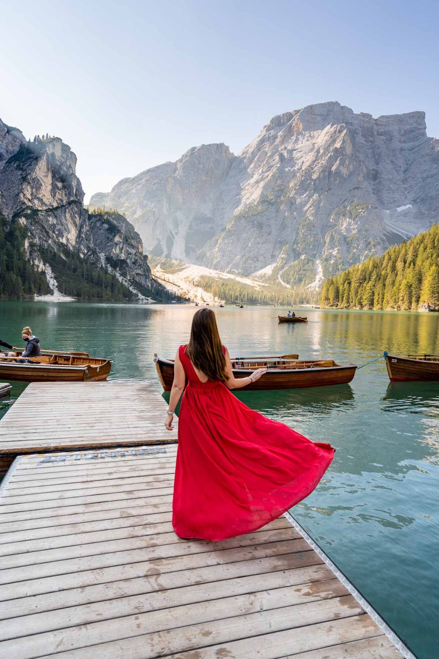 Girl in a red dress standing on the pier at Lago di Braies, which is a must visit on every Dolomites road trip itinerary