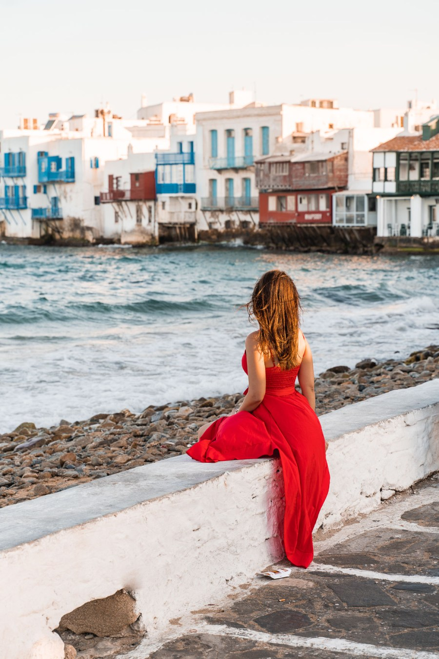 Girl in a red dress sitting at Little Venice in Mykonos Town