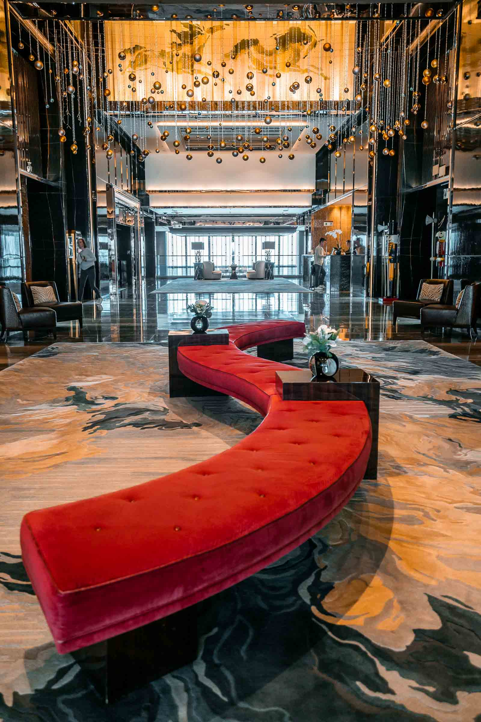 Lobby in the Ritz Carlton Hong Kong with a golden and dark marble design and a big red sofa