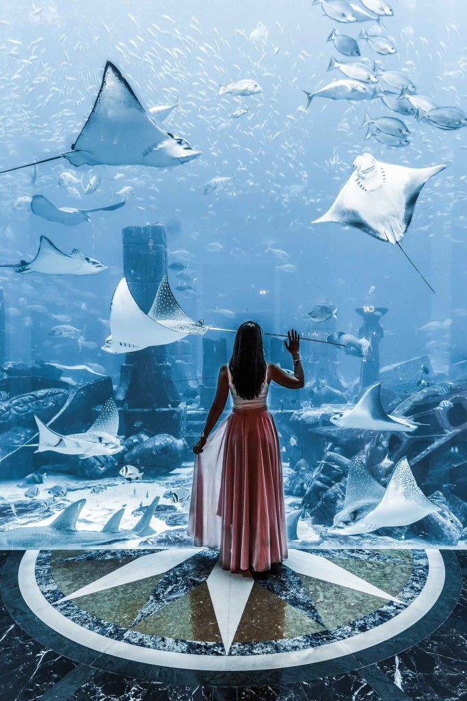 Girl in pink skirt standing in front of a huge aquarium at the Atlantis hotel in Dubai