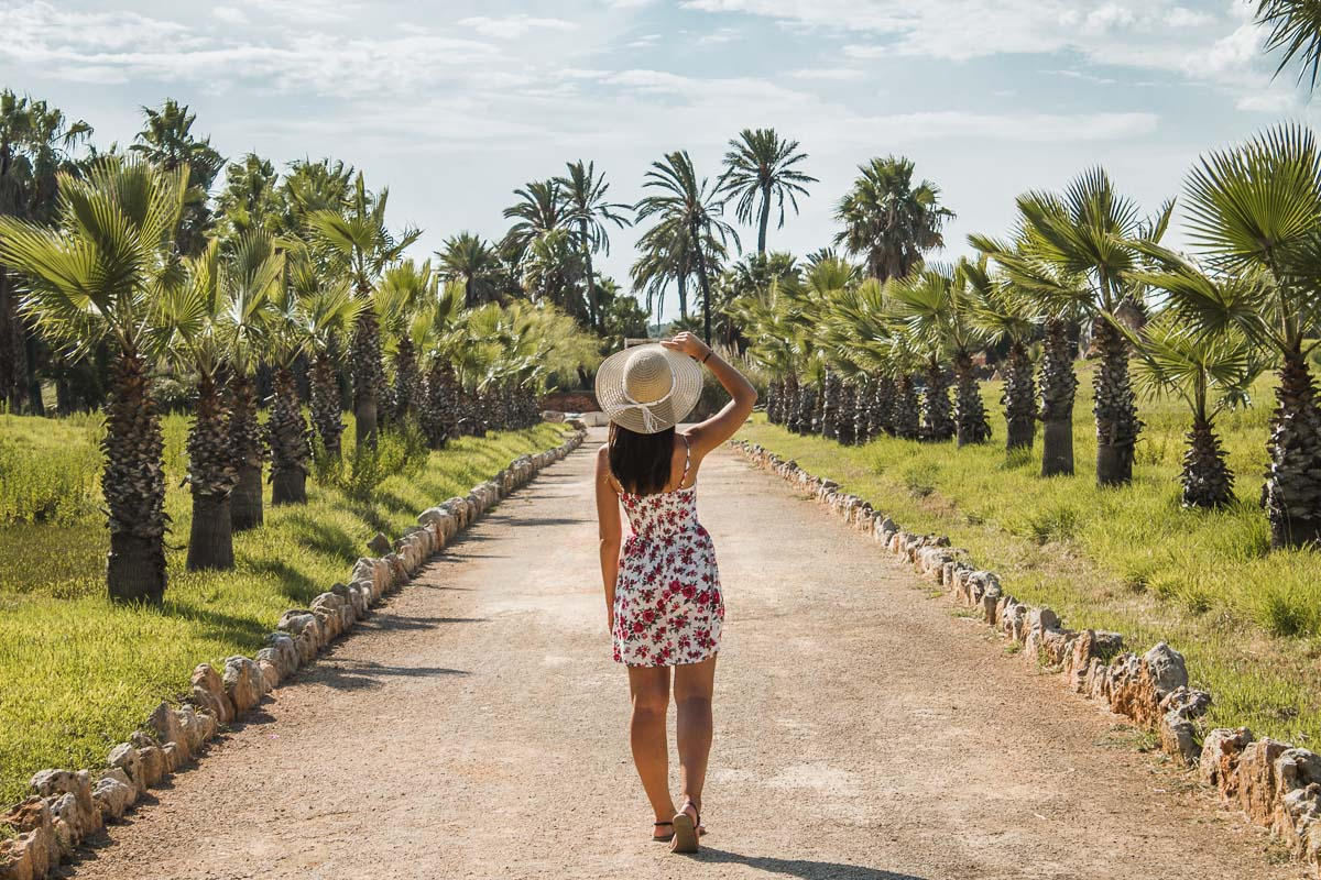 Girl in a floral dress and a straw hat standing in a pathway bordered by palm trees in Mallorca
