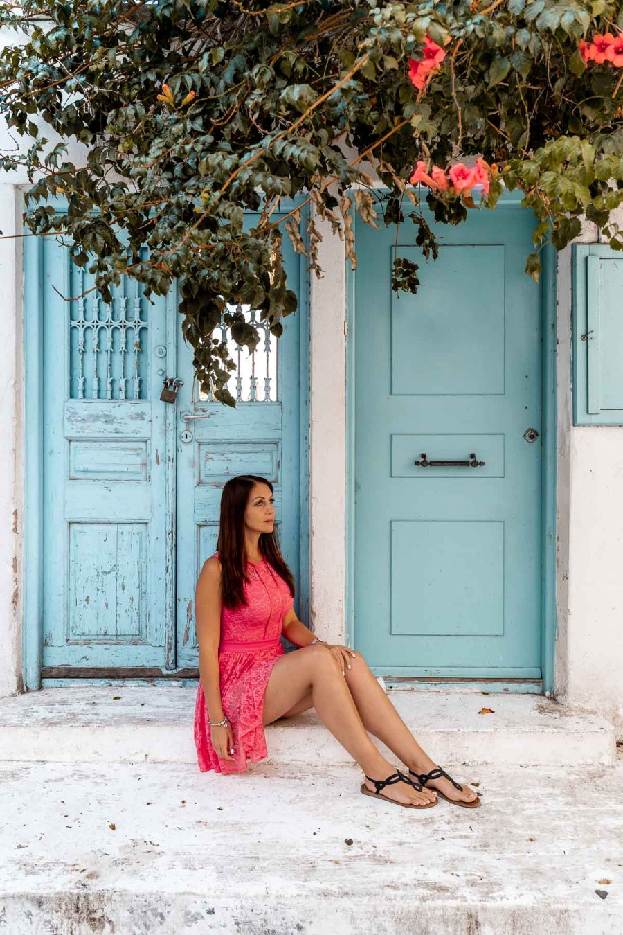 Girl in a pink dress sitting in front of a turquoise door in Mykonos