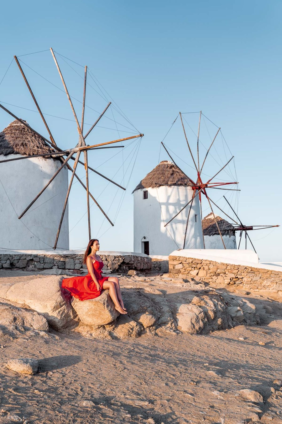 Girl in a red dress sitting on a rock in front of the windmills in Mykonos