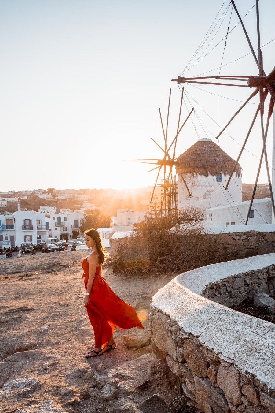Girl in a red dress standing in front of the windmills in Mykonos at sunrise
