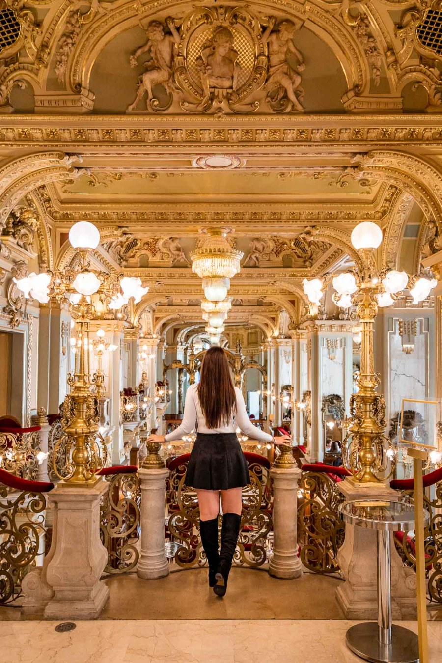 The beautiful interior of New York Cafe Budapest with girl in the middle