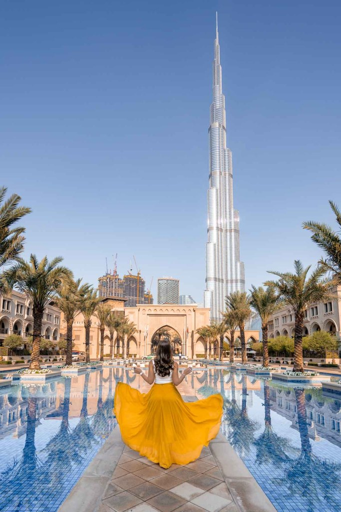 Girl in yellow skirt twirling in front of the Palace Downtown in Dubai with the Burj Khalifa in the background
