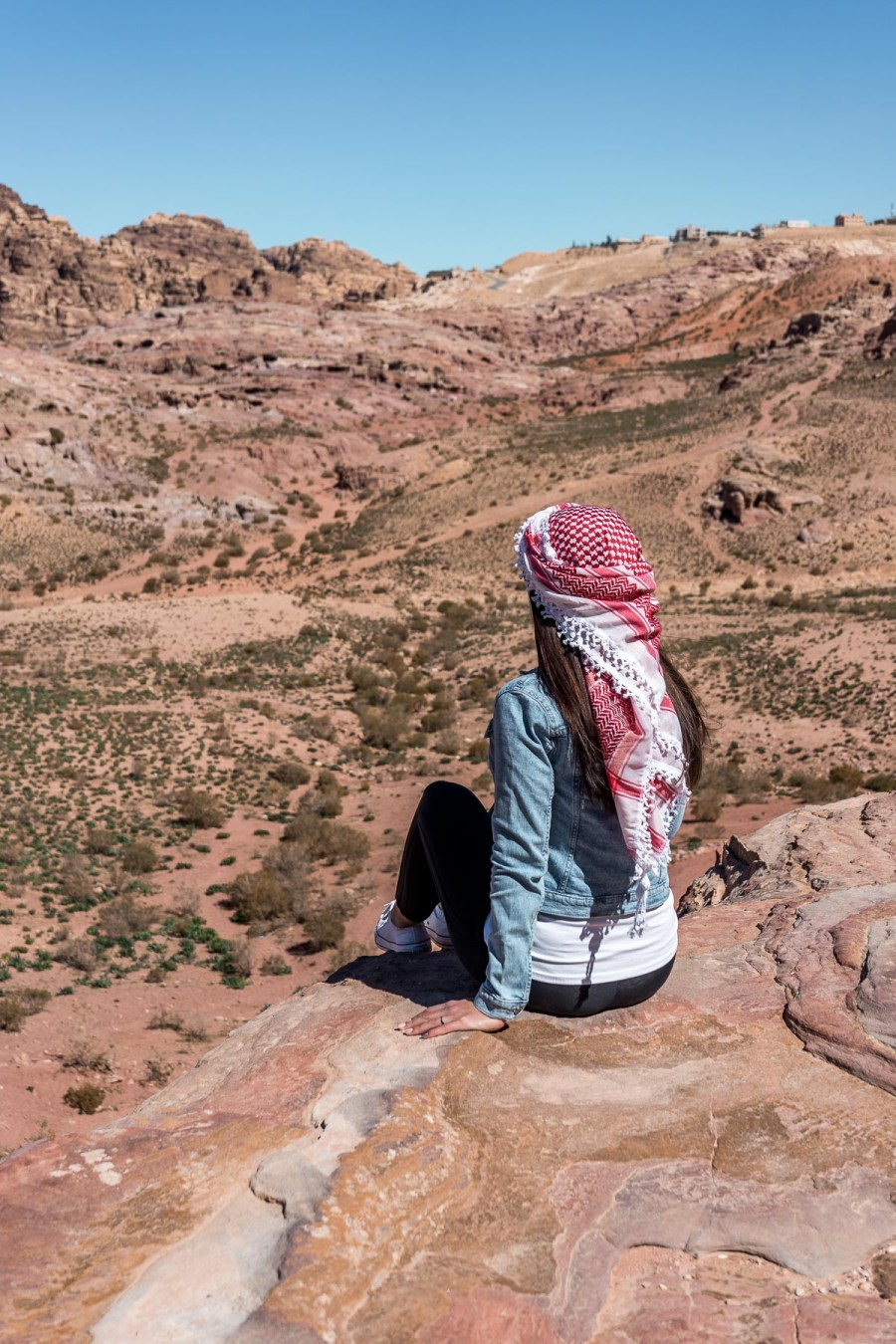 Girl in a denim jacket and a white-red keffiyeh looking at the view in Petra, Jordan