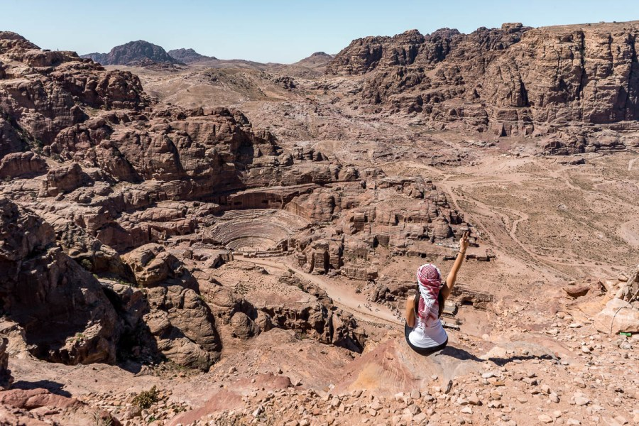 Girl in a white top and a white-red keffiyeh looking at the view in Petra, Jordan