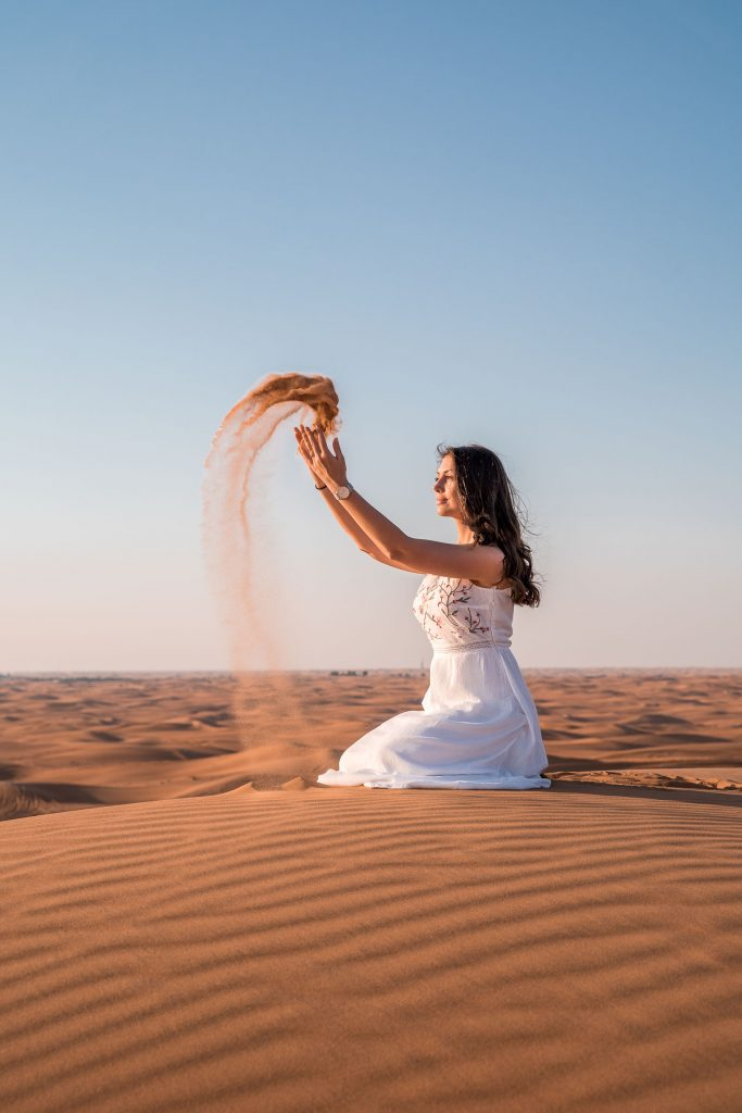 Girl in a white dress throwing sand in the air in the Dubai desert