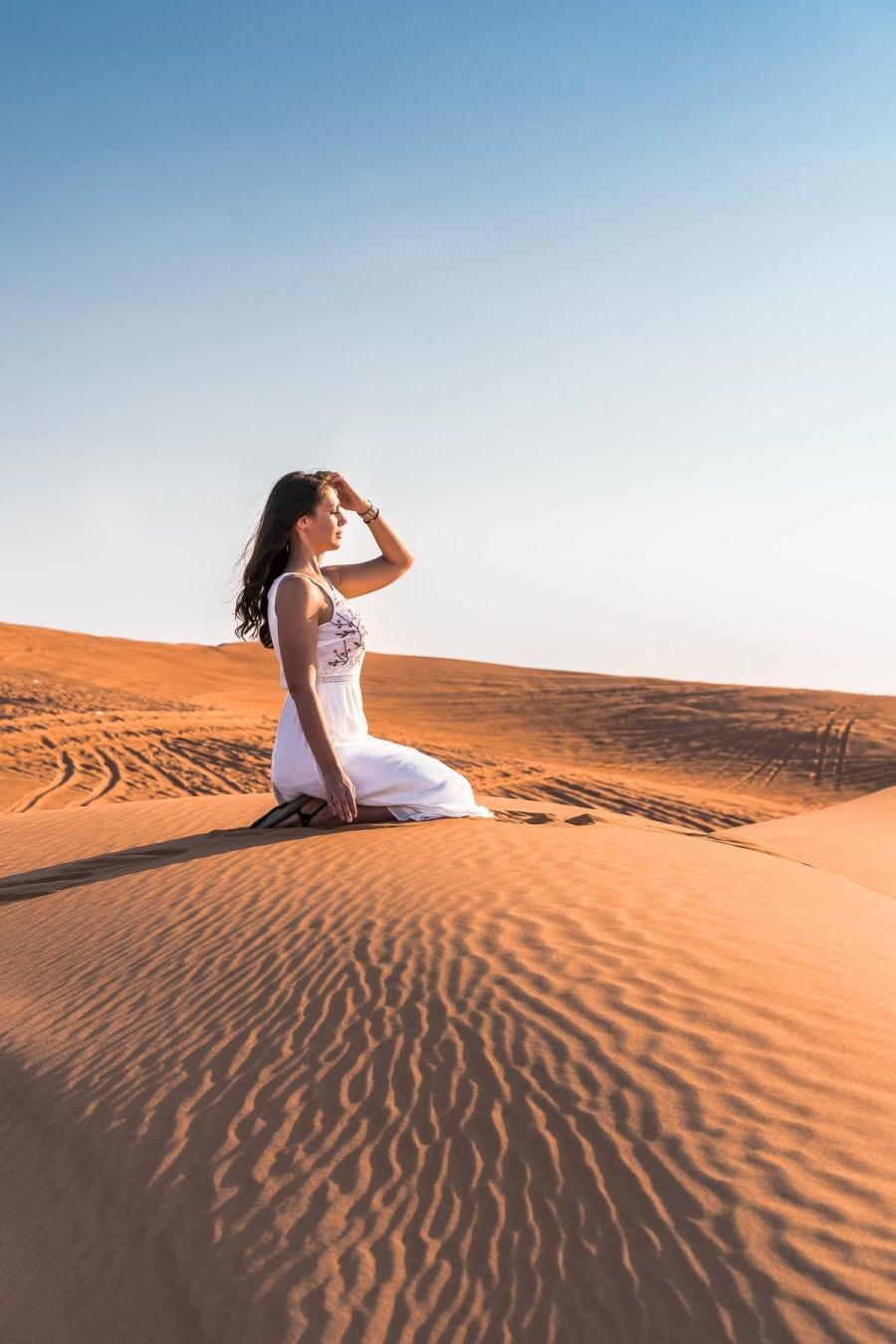 Girl in white dress sitting in the Dubai desert on the sand dunes